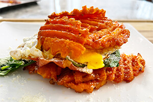 a fried egg, crispy prosciutto, melted Gruyère and sautéed baby spinach layered on a bed of Alexia waffle cut sweet potato fries
